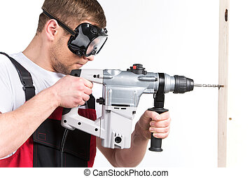 Construction building engineer or manual worker man in safety glasses. male holding electric hammer drill tool on white background