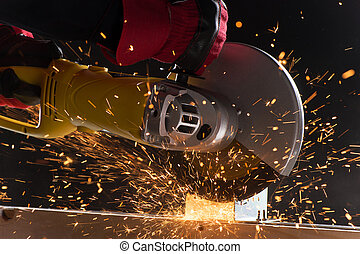 closeup on electric saw and hands of worker with sparks man...