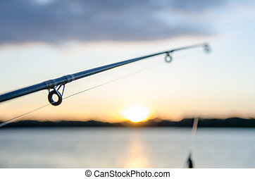 fishing rod with lure at sunset over a lake