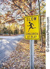 Yellow Slow Children at Play Road Sign and road