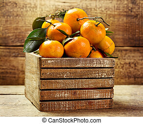 tangerines with leafs in wooden box