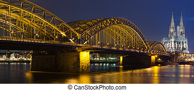 Night panoram of Cologne Cathedral and railway bridge over...