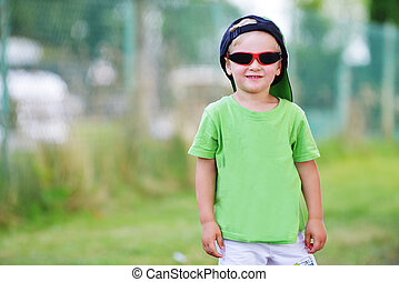 little boy  with sunglasses in summer park