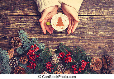 Female holding cup of coffee with cream christmas tree on a...