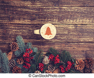 Cup of coffee with cream christmas tree on a table.