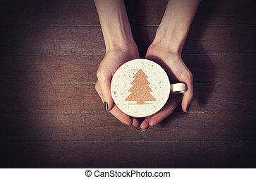 woman holding hot cup of coffee, with christmas tree shape