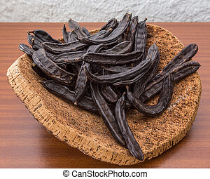 Carob pods on cortical stand On the table