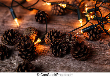 Shiny garland with heap of pinecones on the floor