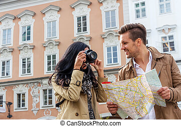 couple on a city break - young couple with map and guide...