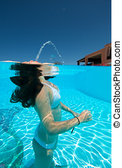 Underwater view of a woman swimming in the swimming pool