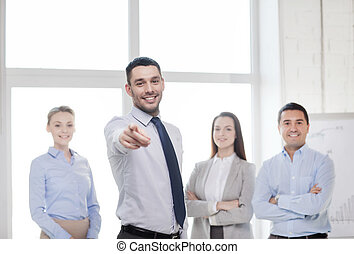 businessman in office pointing finger at you