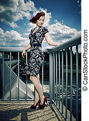 Young woman on floodgate - Nice redhair lady posing in...