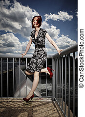 Pretty girl on floodgate - Nice redhair lady posing in...