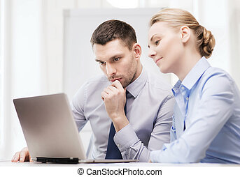 serious business couple with laptop computer - business,...