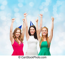 smiling women in party caps showing thumbs up - holidays,...
