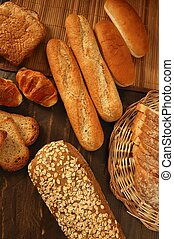 Varied bread still life over dark wood background