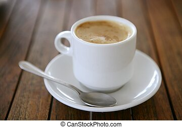 Coffe with milk white cup over teak wooden background