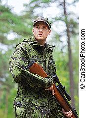 joven, soldado, o, cazador, con, arma de fuego, en, bosque,