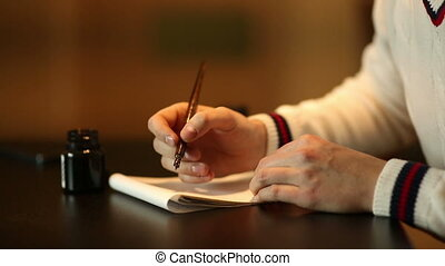Man writining some text by pen. Footage in low key. Indoor...