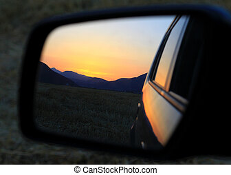 Car rearview mirror sunset