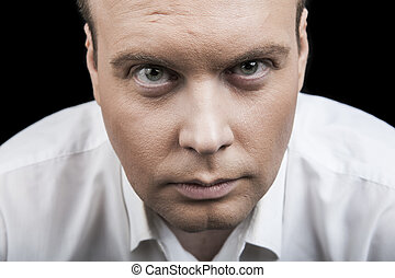 man looking intently into the eyes on a black background