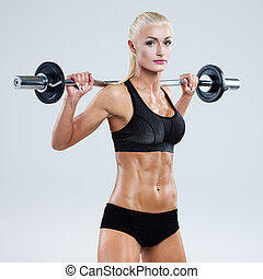 Fitness with barbell - Athletic woman pumping up muscles...
