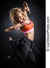 Fitness dancer - Young woman jumps while making aerobics...
