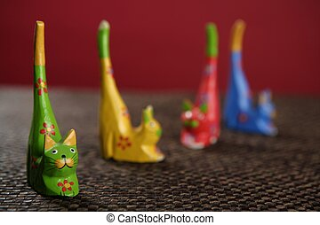 four handcraft cats in colors still over tablecloth - four...