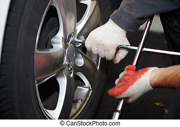 Car mechanic changing tire. - Car mechanic changing tire in...