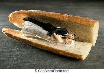 wedding figurine in a bread sandwich - Marriage metaphor,...