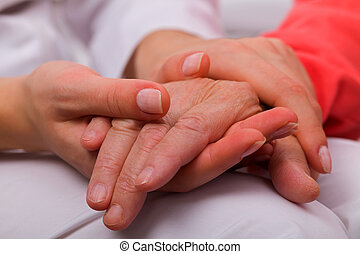 Home care - Caregiver holding elderly patients hand at home