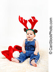 Child girl with Christmas santa hat and reindeer antlers