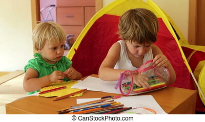 children sketching with paper and pencils in home interior