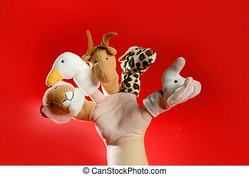 Finger puppets on a toddler hand over red background