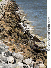 Old Granite Stone Seawall - A rock seawall on the coast in a...
