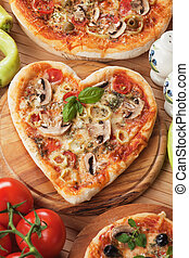 Heart shaped funghi pizza with mushrooms, pepperoni and...