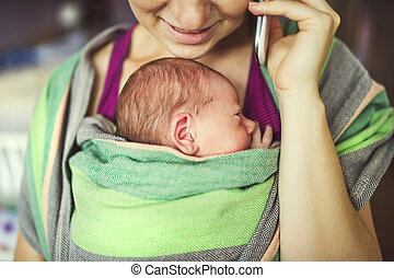 Mother with baby in the wrap carrier - Newborn baby hold by...