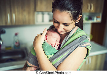 Baby in the wrap carrier - Newborn baby hold by mother in...