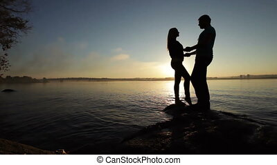 Silhouette of couples at sunset - Loving couple connected...