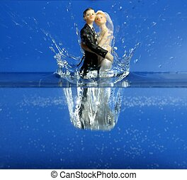 Wedding figurine falling down to blue water, relationship...