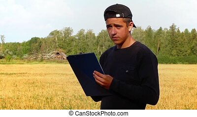 Teen with folder on the field near forest