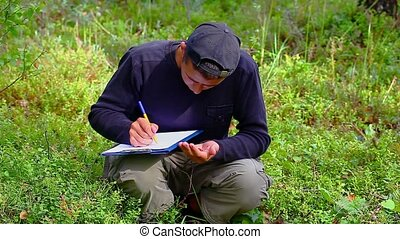 Teen with folder on the cranberries field in forest