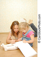 young mother with her daughter lying on the floor and drawing