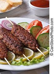 kebabs with ketchup and fresh vegetables vertical - Grilled...