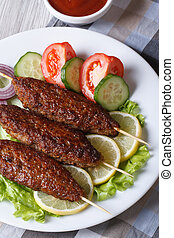 kebabs with vegetables and ketchup closeup. vertical top...