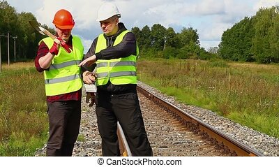 Railroad workers with measuring tap