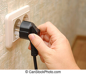 female hand sticks a plug in the socket