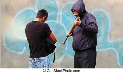 Agressive man with a baseball bat against teenager at...