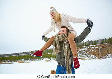 Cheerful winter date - Young man carrying his girlfriend on...