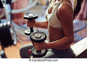 Training with dumbbells - Young woman exercising with...